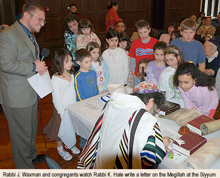 Rabbi Joshua Waxman and congregants watch Rabbi Kevin Hale write a letter on the Megillah at the Siyyum